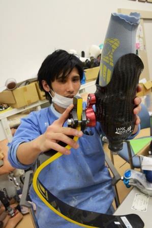 競技用の義足を手にしている義肢装具士 藤田悠介さん