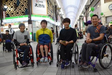 写真左から、小島将平選手、西勇輝選手、鈴木朋樹選手、佐藤健選手。 関東を拠点している車いす陸上の仲間たちとともに。 2015年大分国際車いすマラソン大会開会式の会場にて。